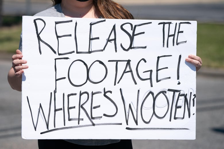 A demonstrator holds a sign addressing Pasquotank County Sheriff Tommy Wooten after an emergency city council meeting April 23, 2021 in Elizabeth City, North Carolina.