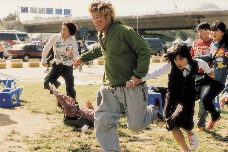 In a scene from The Host, Song Kang-ho, Ko A-sung, and others flee, running in front of a parking lot.