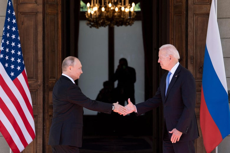 Biden and Putin walking toward each other to shake hands