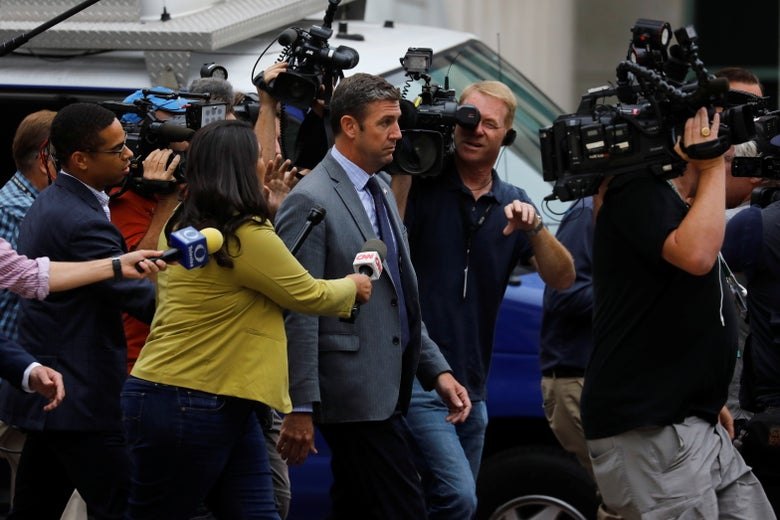 Hunter walks while being surrounded by a crowd of reporters.
