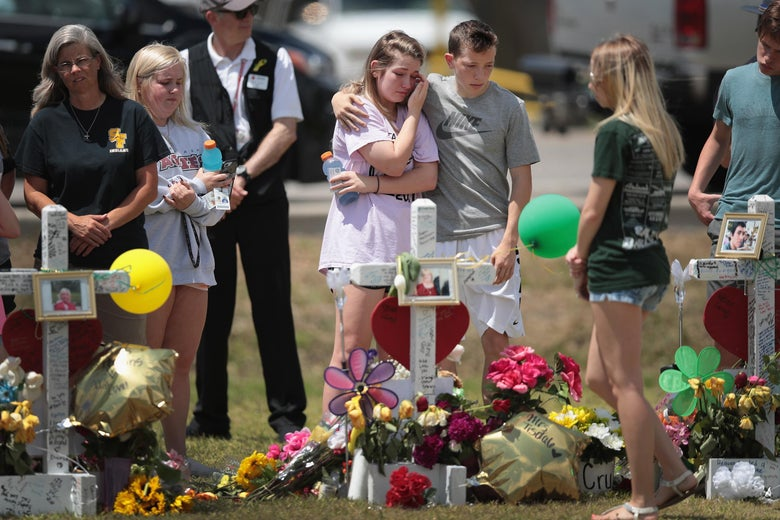 SANTA FE , TX - MAY 22:  Mourners visit a memorial in front of Santa Fe High School on May 22, 2018 in Santa Fe, Texas. The makeshift memorial honors the victims of last Friday's shooting when 17-year-old student Dimitrios Pagourtzis entered the school with a shotgun and a pistol and opened fire, killing 10 people.  (Photo by Scott Olson/Getty Images)