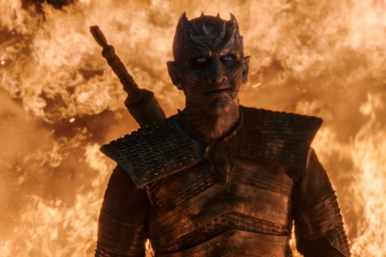 The Night King stands before a wall of fire, with a smirk on his face.
