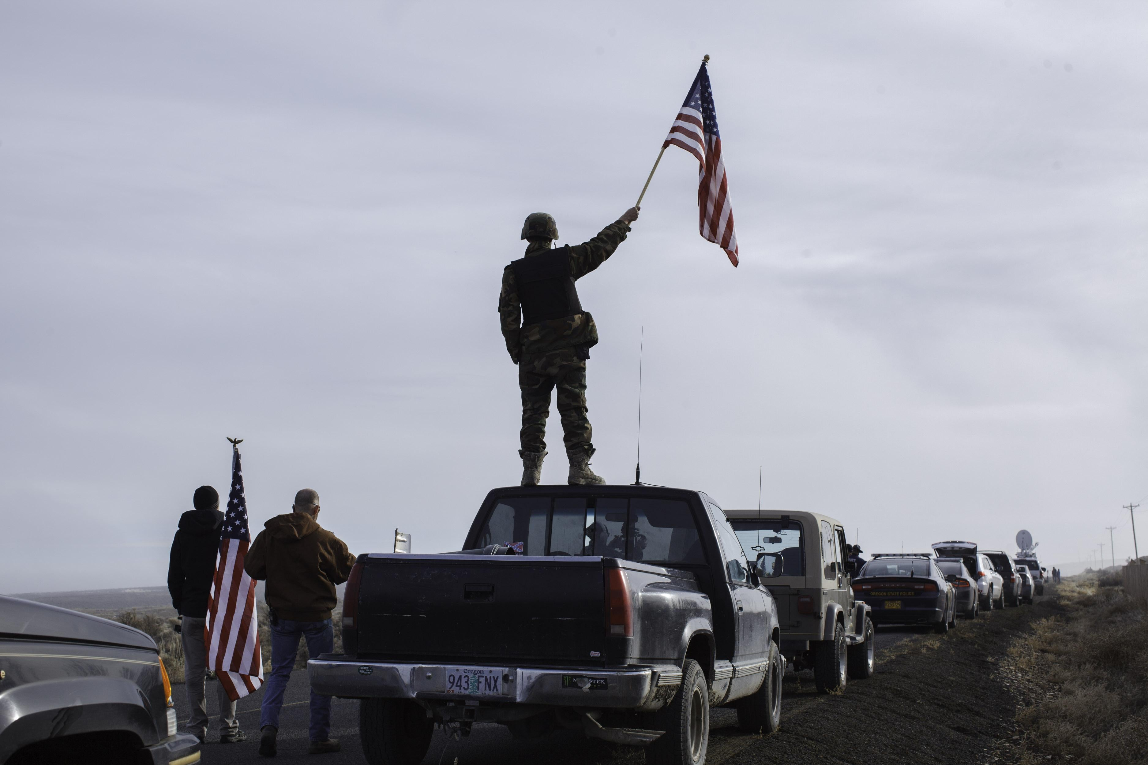 A protester dressed in military gear stands on top of a pickup truck holding an American flag.