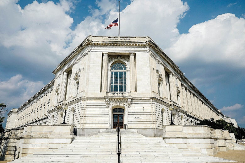 The United States flag flies at half-staff over the Russell Senate Office Building on Capitol Hill in honor of Sen. John McCain on Monday in Washington.
