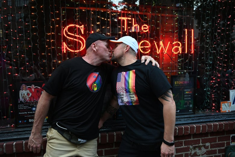 Two people kiss in front of the Stonewall Inn bar during Pride celebrations.