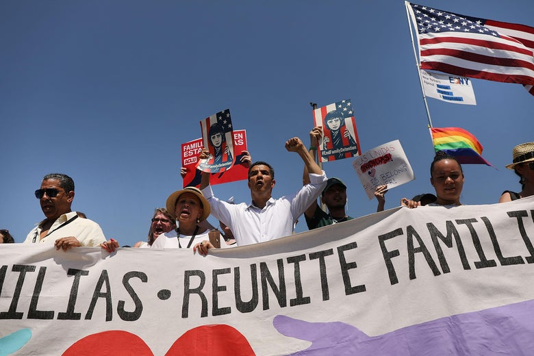 "Protesters march with a banner that says ""Reunite Families."""
