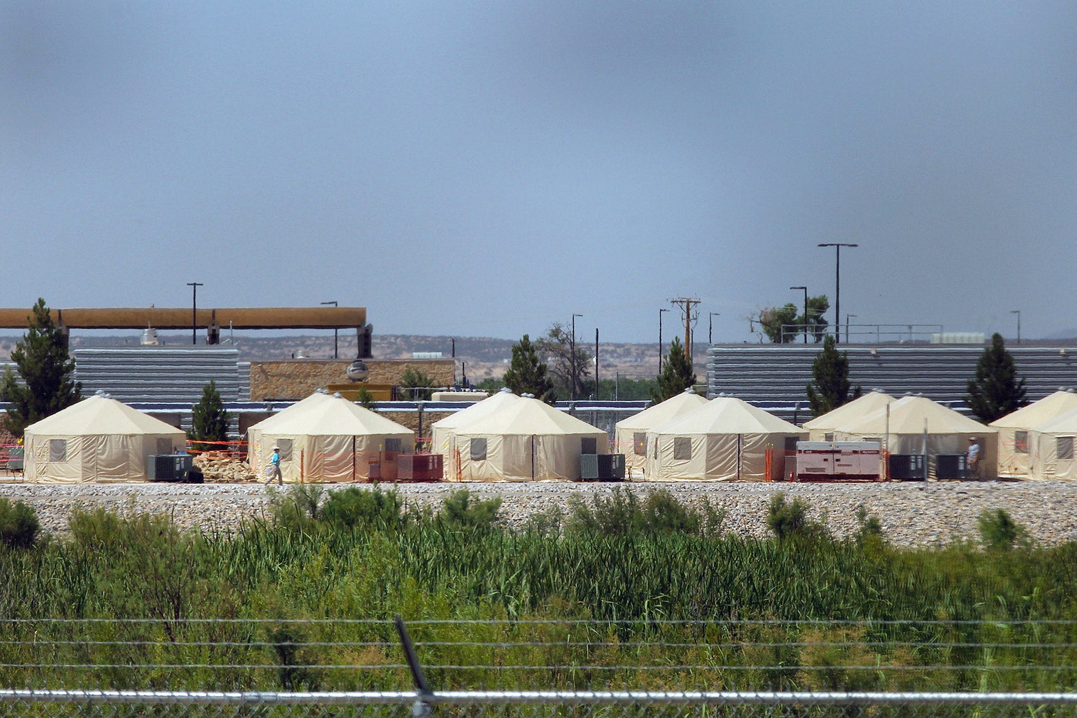 Behind barbed wire, tents are set up as a temporary detention center.