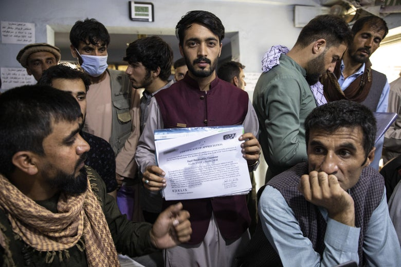 A man looks directly at the camera holding up his certificate amid a crowd of people