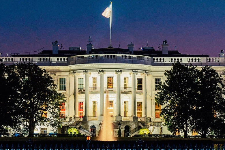 The White House, illuminated brightly against a purple-blue night sky.