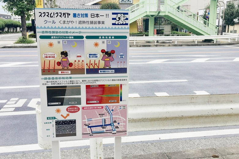 Heatstroke warning poster in Japanese beside a road