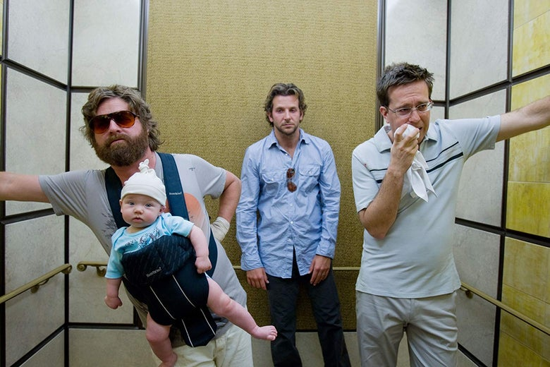 Three men in an elevator. One wears a baby in a carrier on his chest.