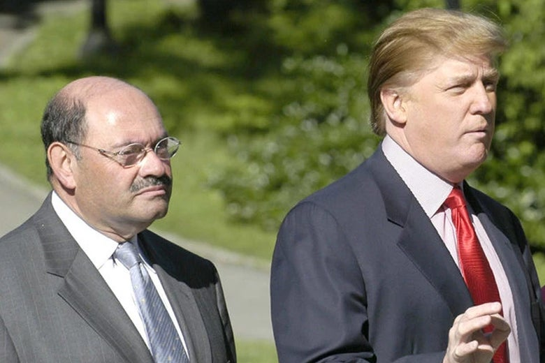Weisselberg, a shorter bald man with a mustache, stands next to Trump while Trump gestures.