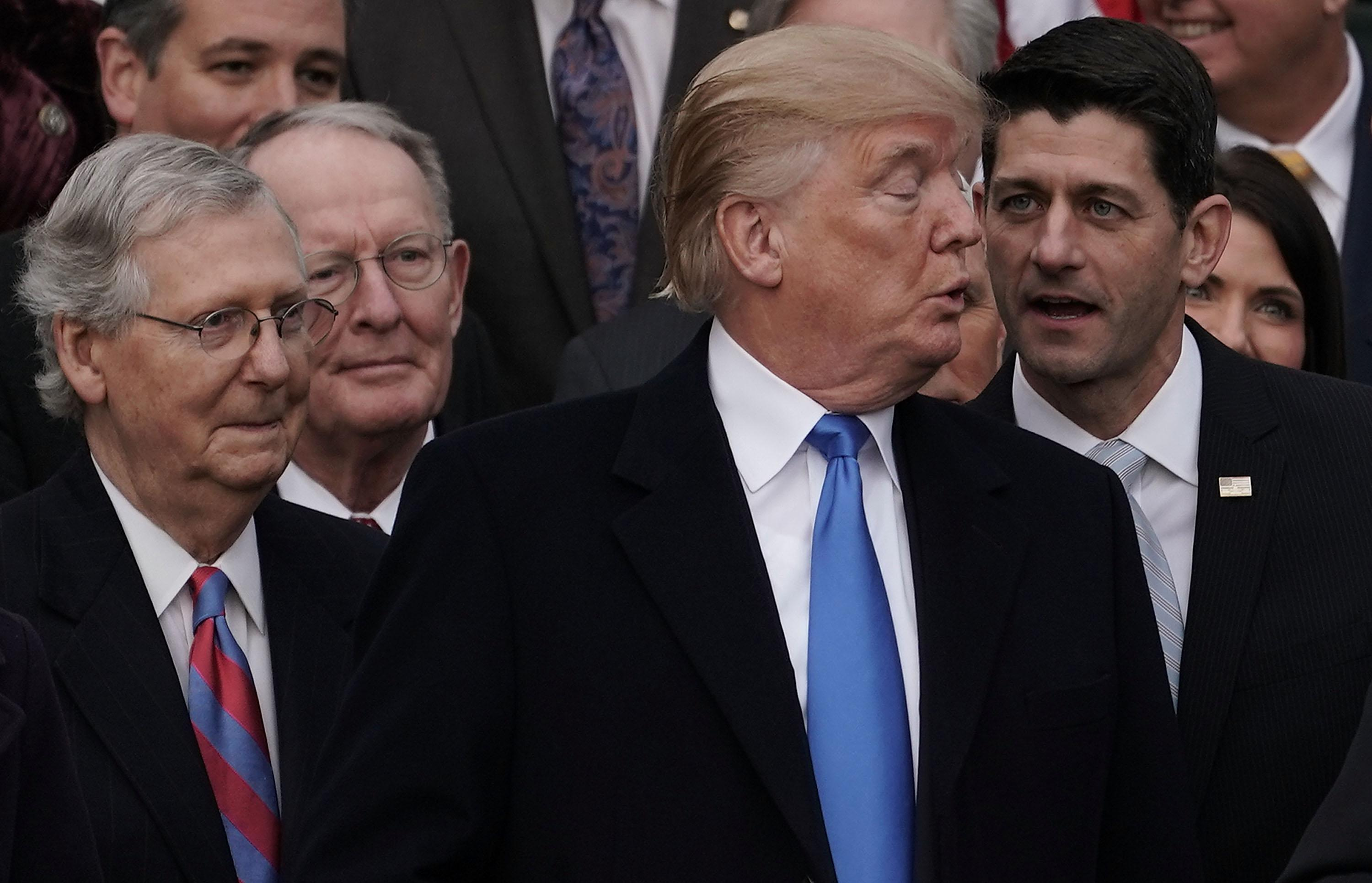 WASHINGTON, DC - DECEMBER 20:  U.S. Speaker of the House Rep. Paul Ryan (R-WI) talks to President Donald Trump (3rd L) as Senate Majority Leader Sen. Mitch McConnell (R-KY), and Sen. Lamar Alexander (R-TN) (2nd L) look on during an event to celebrate Congress passing the Tax Cuts and Jobs Act with Republican members of the House and Senate on the South Lawn of the White House December 20, 2017 in Washington, DC. The tax bill is the first major legislative victory for the GOP-controlled Congress and Trump since he took office almost one year ago.  (Photo by Alex Wong/Getty Images)