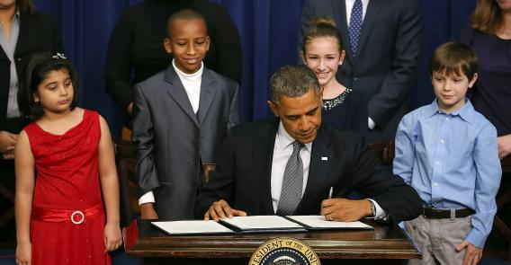 U.S. President Barack Obama signs a series of executive orders about the administration's new gun law proposals as children who wrote letters to the White House about gun violence (from left) Hinna Zeejah, Taejah Goode, Julia Stokes, and Grant Fritz, look on, Jan. 16, 2013