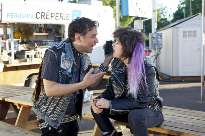 Brownstein and Armisen, in character as punks (with stereotypical jean jackets, studded accessories, and colored hair) argue into a cell phone.
