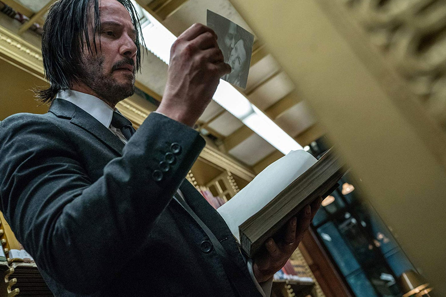 John Wick looks at a photo found inside a book, as he stands in the stacks of a library.