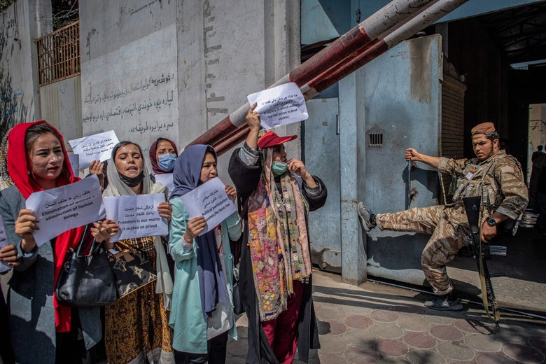A Taliban fighter watches as Afghan women hold placards during a demonstration demanding rights for women in front of the former Ministry of Women Affairs in Kabul on September 19, 2021.
