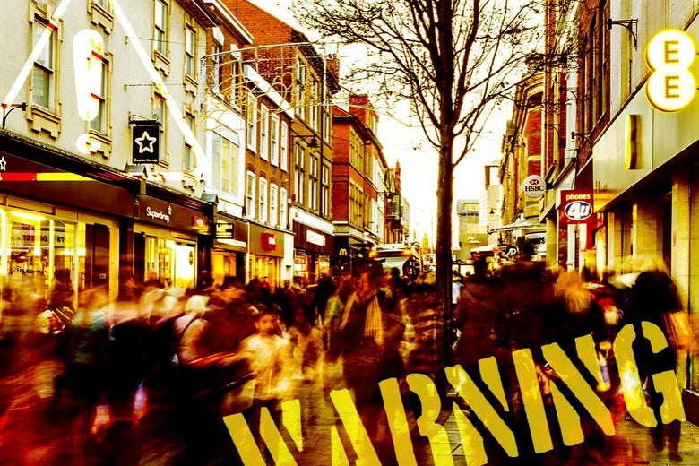 A busy commercial street with the word WARNING on it.