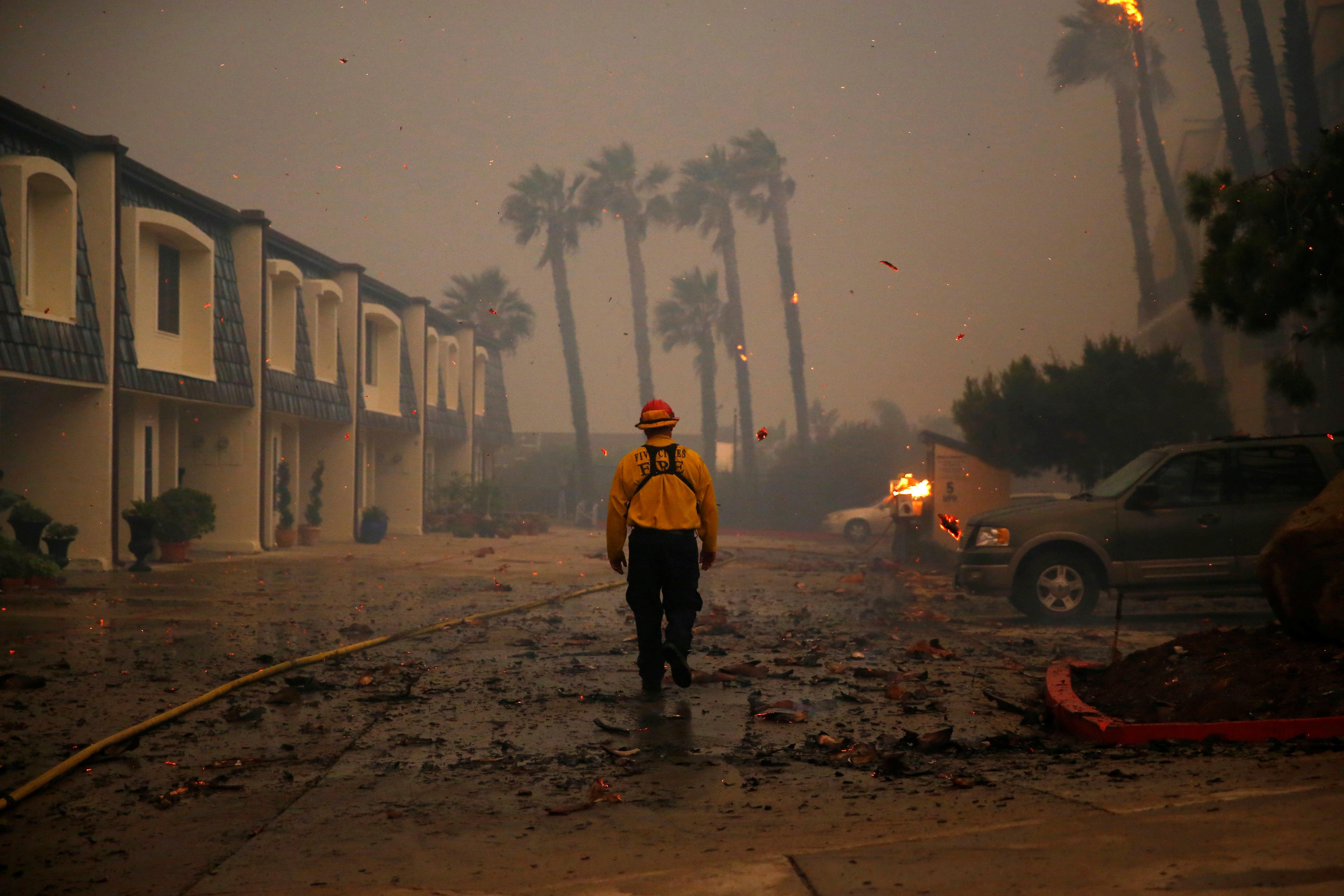 A firefighter walks through a parking lot as the fire burns nearby.