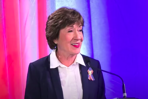 Susan Collins, in a blue suit jacket, white shirt, and American flag lapel ribbon, smiles behind a microphone against a backdrop of red, white, and blue curtains.