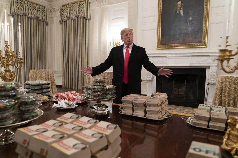 Trump stands behind a table in the White House laden with fast food packages.