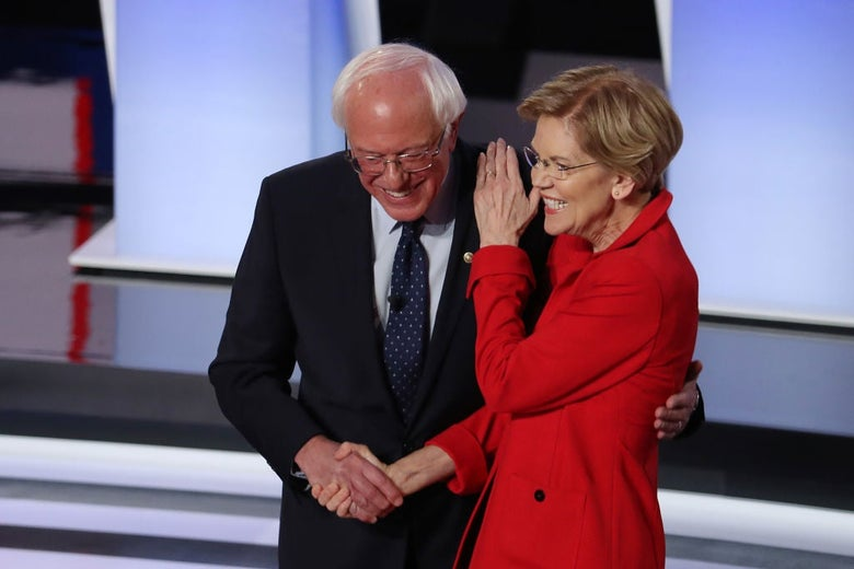 Warren and Sanders both smile as they shake hands onstage and she pats his shoulder.