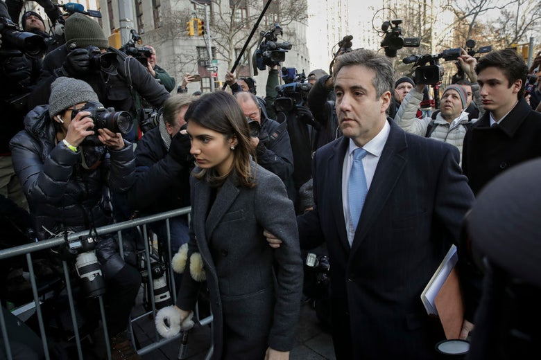 Cohen walks past a barricade amid a crowd of photographers while holding his daughter's arm.