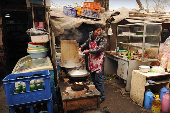 A woman cooks in an outside restaurant on a street in Beijing.