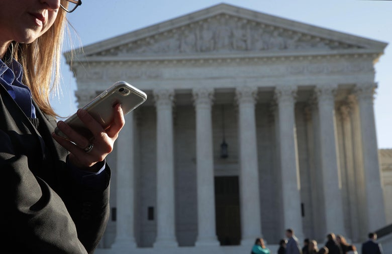 A woman checks her cell phone as she waits in line to enter the U.S. Supreme Court.