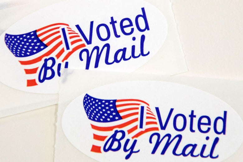 "Stickers that read ""I Voted By Mail"" sit on a table."