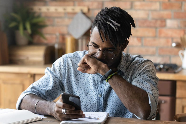 A Black man seated at a table with notebooks in front of him holds one hand up to his mouth and looks at his smartphone, which is held in the other hand.
