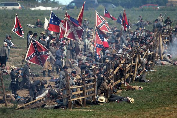 A reenacted Civil War battle, featuring soldiers with rifles and horses waving Confederate flags.