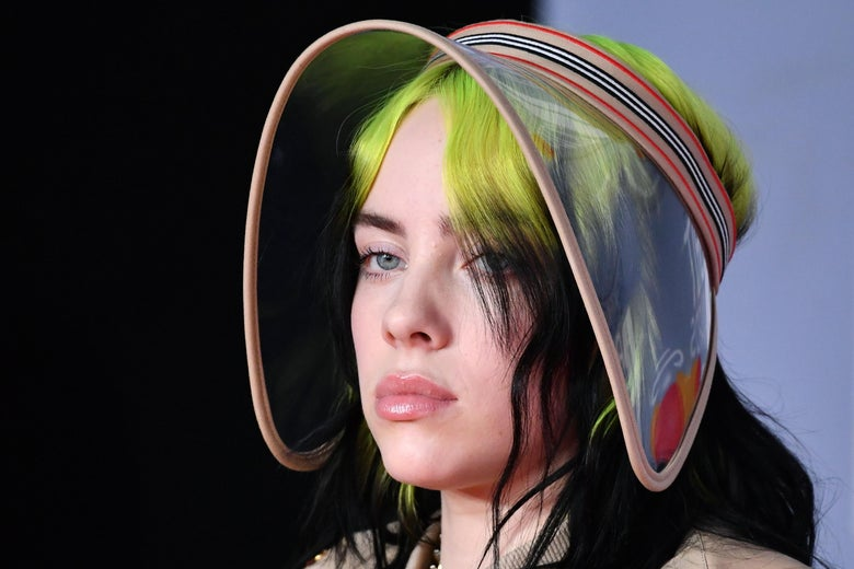 Pouting Billie Eilish, her hair black with green roots, wearing a visor.
