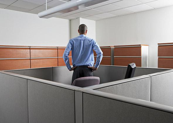 Businessman standing at his desk, trapped in cubicle, rear view