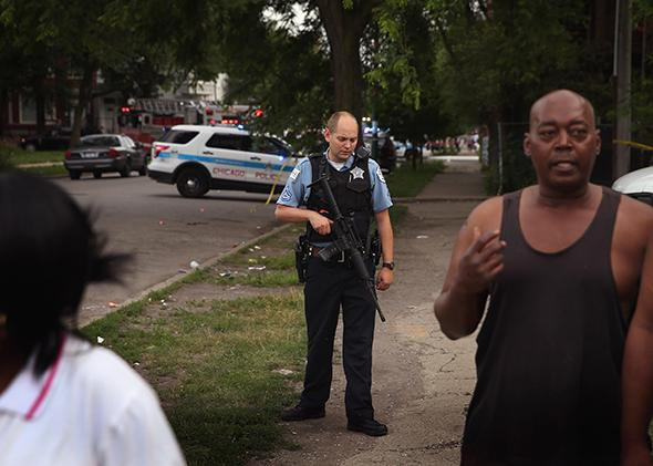 A police officer guards a crime scene where seven people were shot on July 6, 2013, in Chicago.