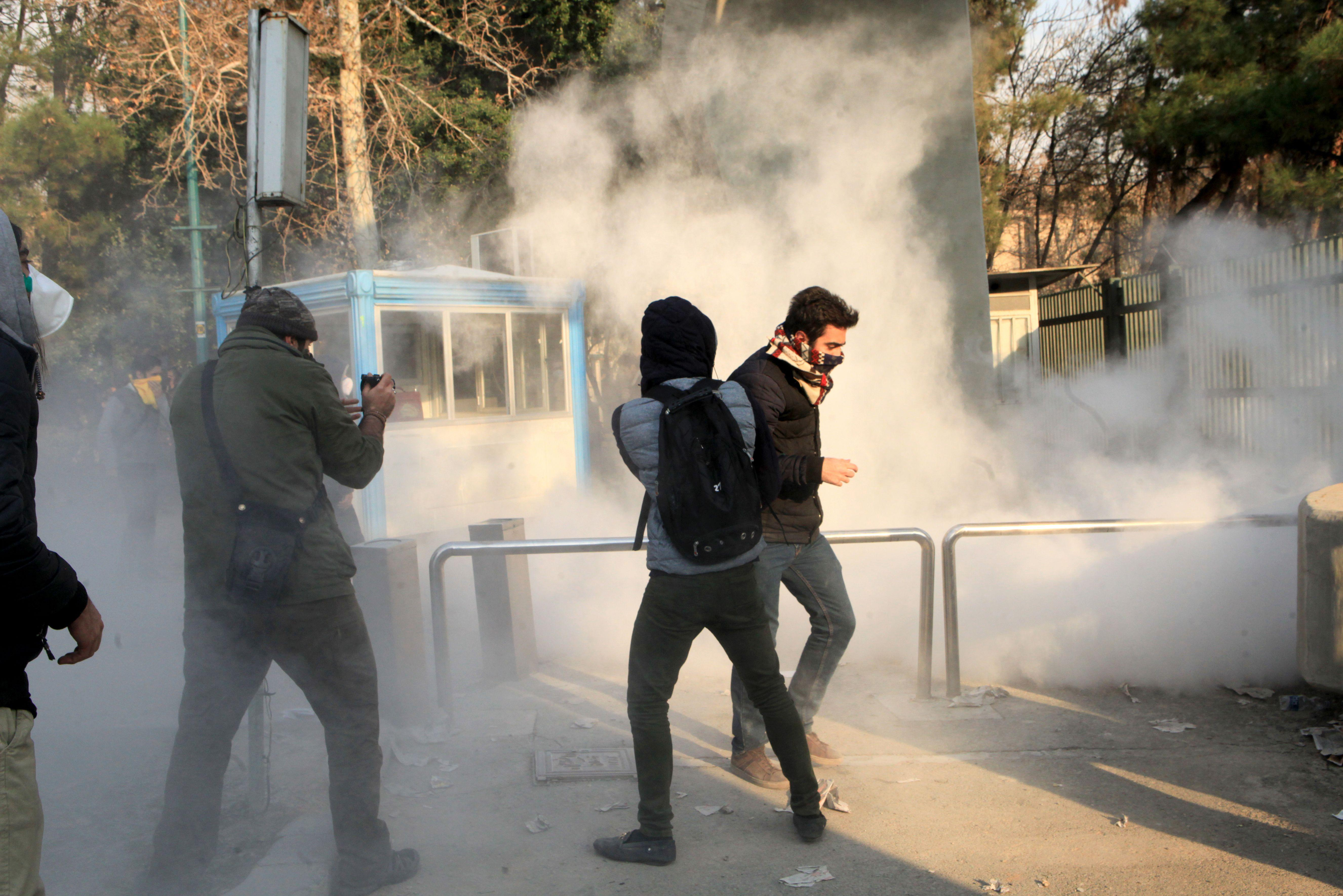 Iranian students run for cover from tear gas at the University of Tehran during a demonstration driven by anger over economic problems, in the capital Tehran on December 30, 2017. Students protested in a third day of demonstrations, videos on social media showed, but were outnumbered by counter-demonstrators.  / AFP PHOTO / STR