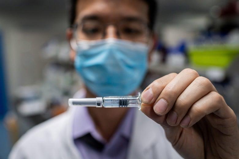 A masked engineer holds a syringe