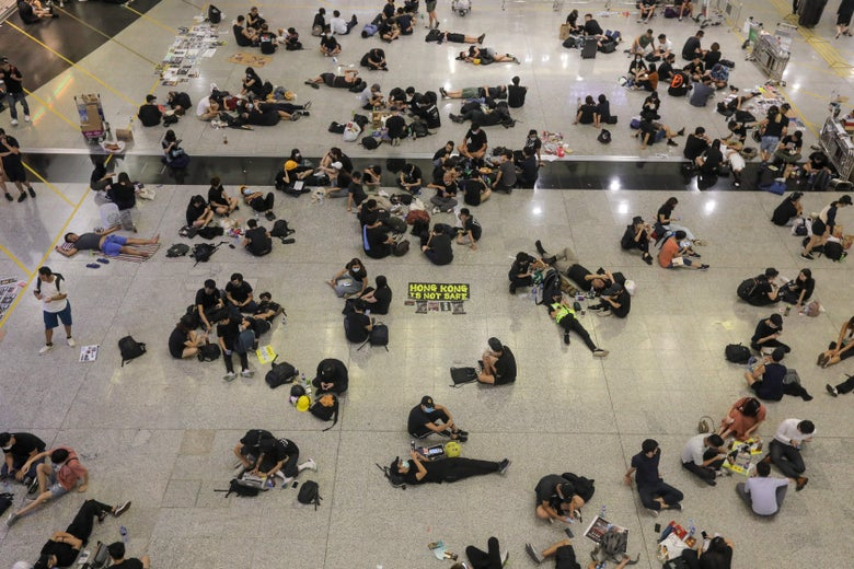 Protesters sit on the floor of the arrivals hall of the airport.