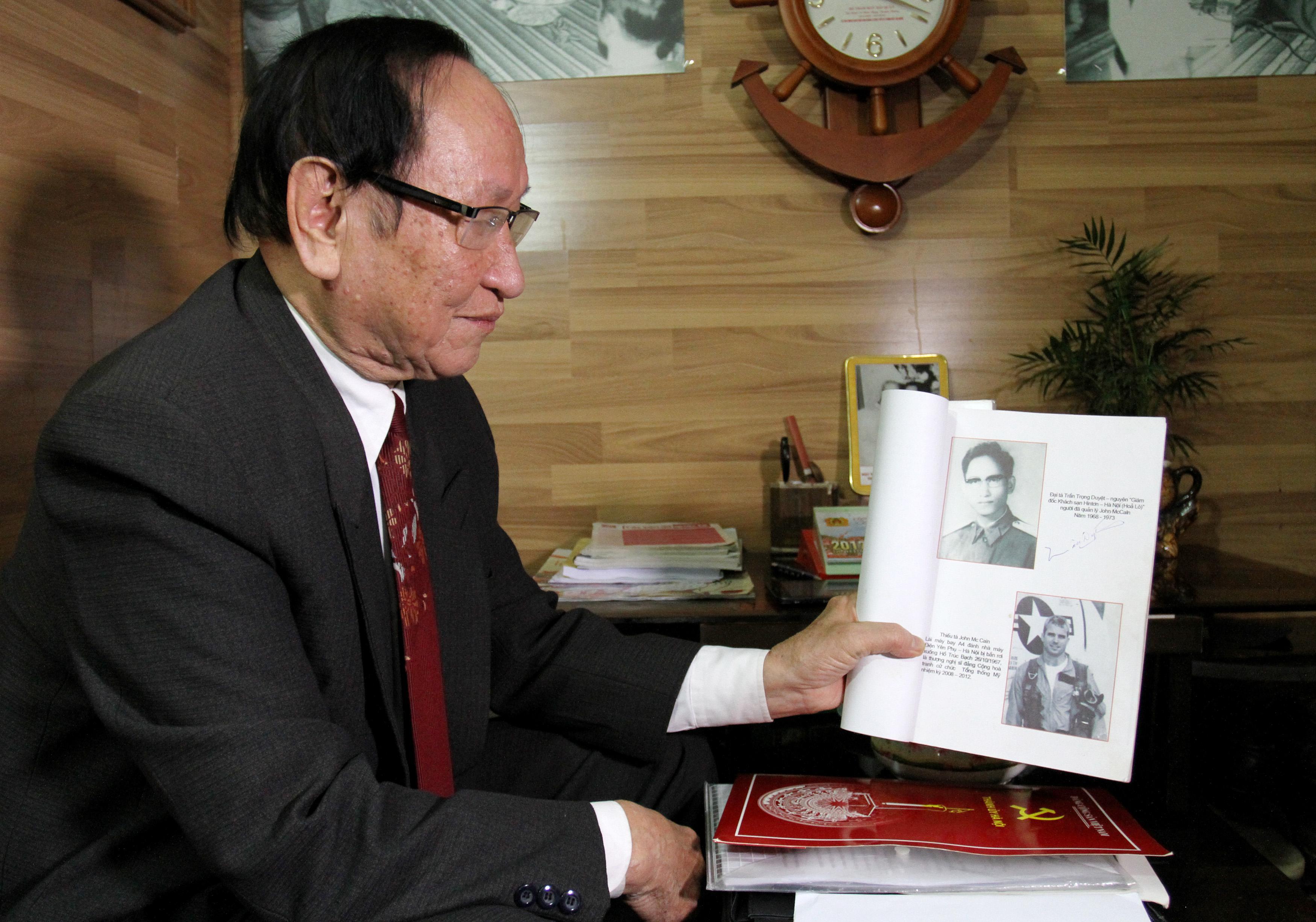 Tran Trong Duyet showing a photo of Sen. John McCain as a young pilot.