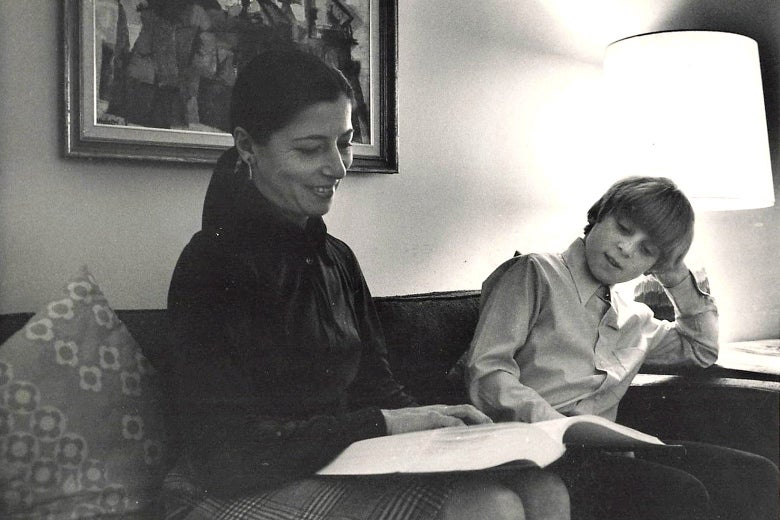 A black-and-white photo in which RBG sits on the couch with a book open next to her young son.
