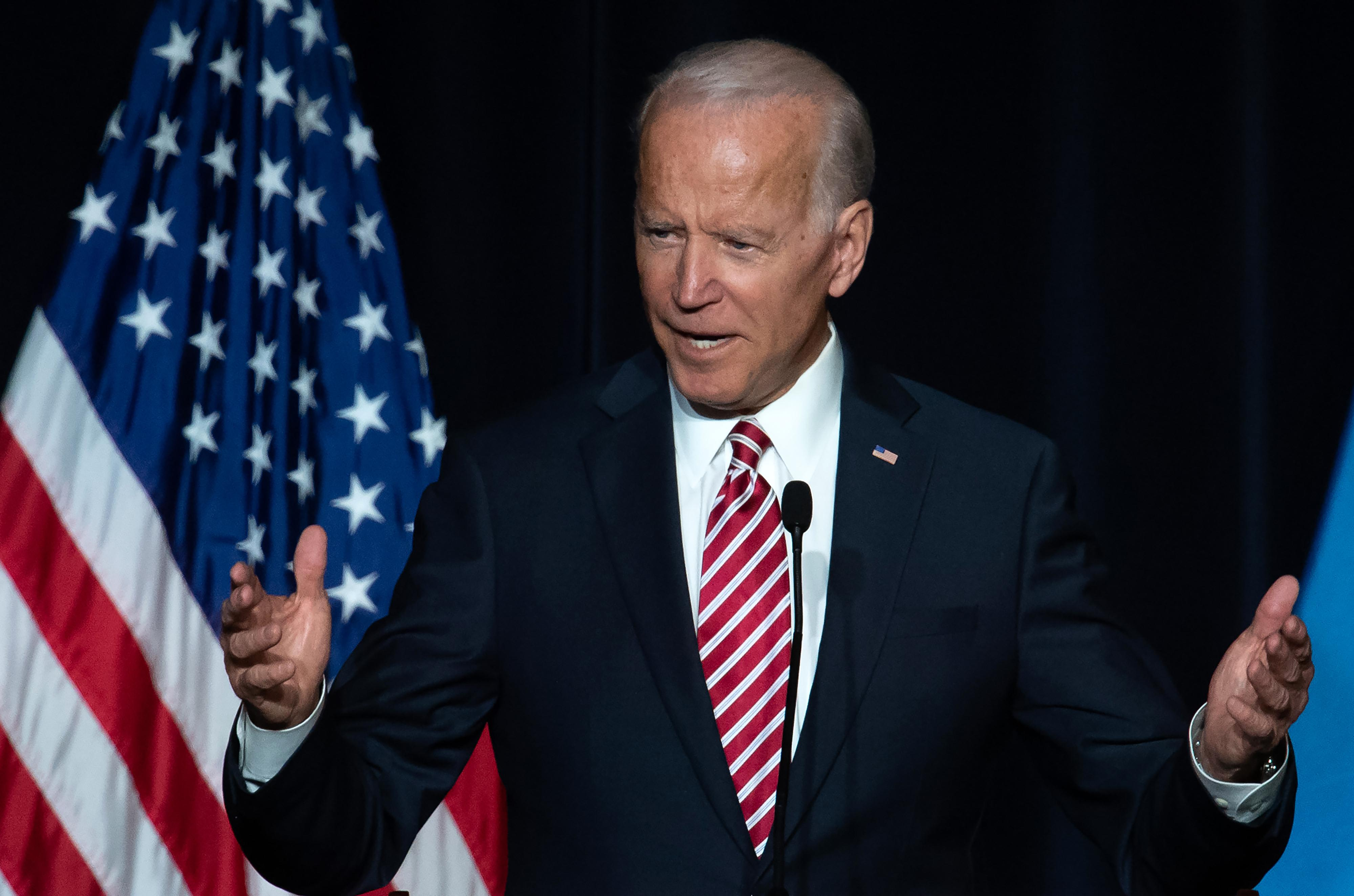 Joe Biden speaks while standing on a stage at a political event.