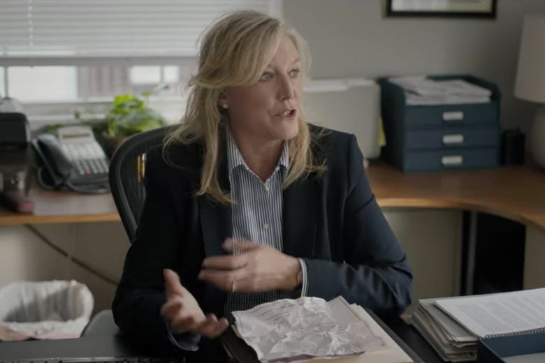 Bill's lawyer sitting behind a desk in an office.