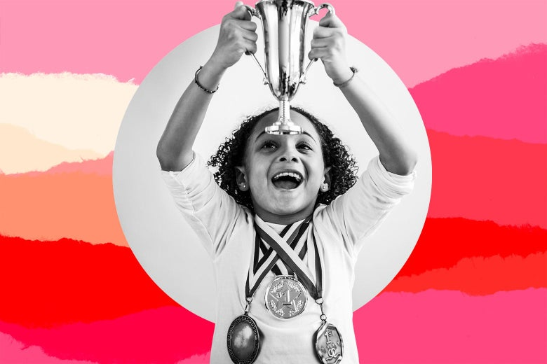 A young girl wearing three medals around her neck and happily holding up a small trophy.