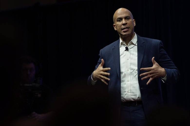 Cory Booker stretches out his fingers while speaking on a stage.