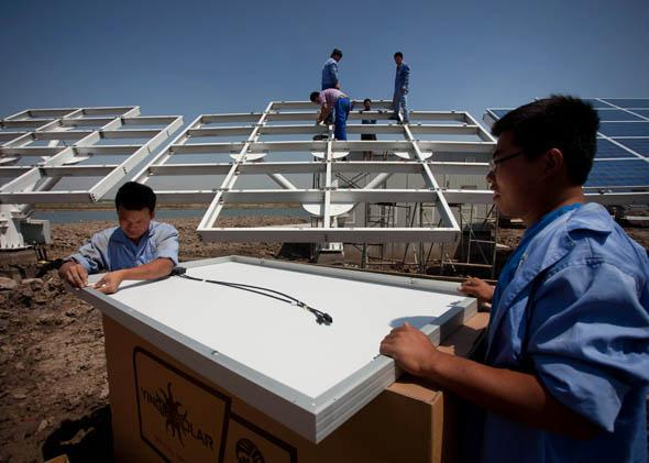 Workers install solar panels near the Sino-Singapore Eco-city near Tianjin, June 11, 2012.