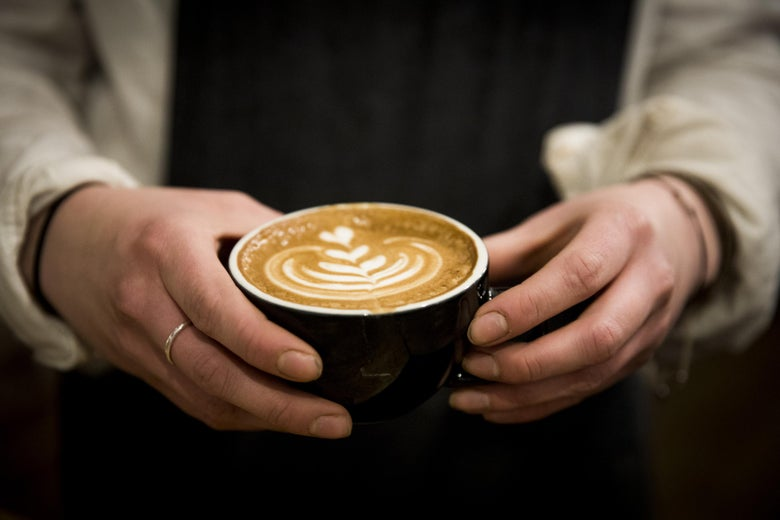 Hands holding a cafe latte.