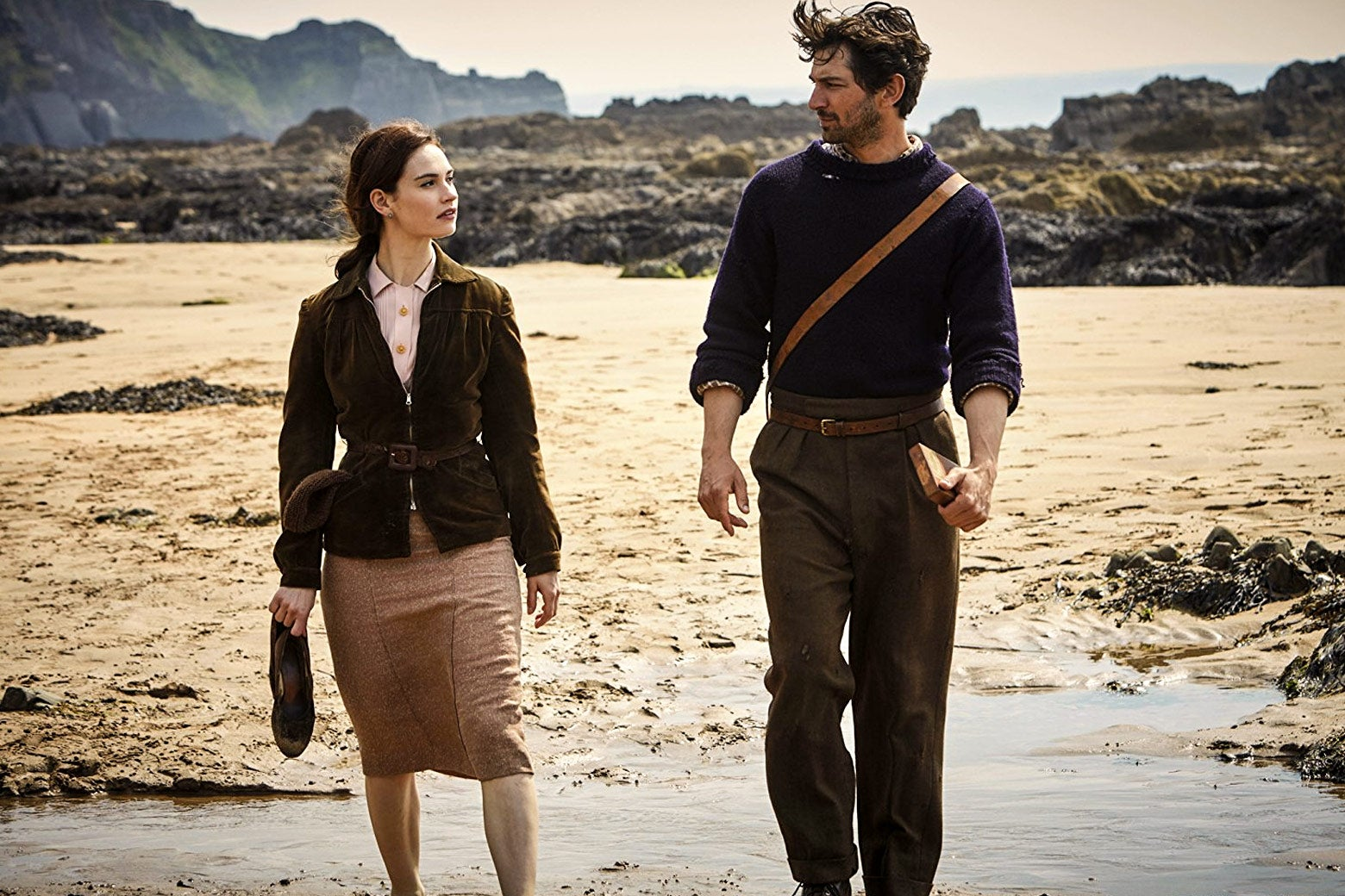 Lily James and Michiel Huisman walk on the beach in The Guernsey Literary and Potato Peel Society.