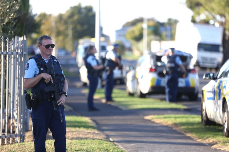 An armed officer holds his rifle while standing guard outside a fenced property. Other police and their vehicles can be seen in the background.