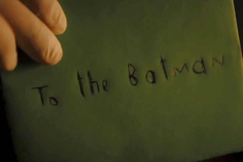 "A hand in a rubber glove holds up a greeting card envelope with ""To the Batman"" scrawled on it."