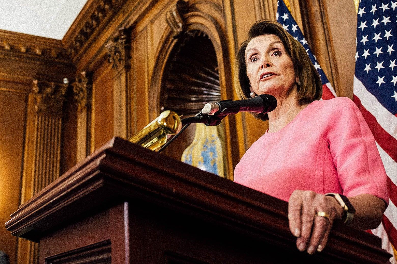 Pelosi speaking at a podium.